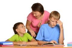 与家庭作业的母亲帮助的孩子 免版税图库摄影
