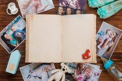 与家庭图片和辅助部件的开放葡萄酒册页在木背景 库存照片