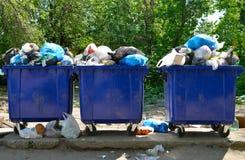 与家庭废物的溢出的垃圾桶在城市 库存图片