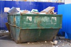 与家庭废物的溢出的垃圾桶在城市 免版税库存照片
