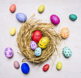 绘与家庭成员装饰鸡蛋的面孔复活节的,在巢木土气背景顶视图关闭 免版税库存图片