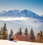 与家庭的冬天场面在山 免版税库存照片