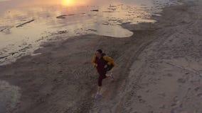 与寄生虫的空中摇摄在一种连续实践锻炼的一名可爱的白种人体育赛跑者妇女在日落与 影视素材