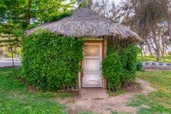 与密集的绿色植物围拢的闭合的木白色难看的东西门的木小屋在一个公园 图库摄影