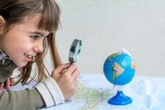 与寸镜的被集中的七岁的女孩审查的地球 库存照片