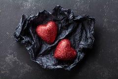 与对的情人节背景在黑纸的发光的心脏从上面 库存图片
