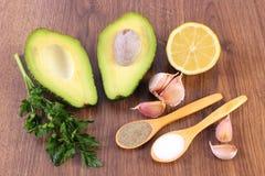 与对鲕梨酱的成份的鲕梨和香料或鳄梨调味酱捣碎的鳄梨酱、健康食物和营养 免版税库存图片