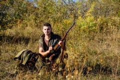 与寻找动物的步枪的猎人 准备好猎人卡其色的衣裳寻找自然背景 狩猎射击战利品 人 免版税图库摄影