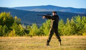 与寻找动物的步枪的猎人 狩猎射击战利品 狩猎的人步枪 寻找的心里准备 库存照片
