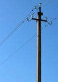 与导线和绝缘体的电杆反对蓝天 免版税库存图片