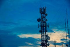 与导线的电信塔和Anntenas有黄昏天空背景、线空中结构和子线,收音机Frecuency 免版税库存照片