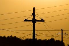 与导线的电杆在金黄日落 图库摄影