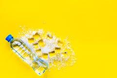 与封锁的被碰撞的冰块在黄色厨房用桌顶视图嘲笑 免版税库存图片