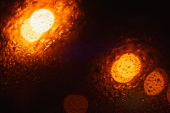 与小下落的红色闪烁光bokeh背景在黑夜 纹理,抽象 图库摄影