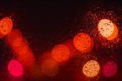与小下落的红色闪烁光bokeh背景在黑夜 免版税库存图片