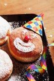 与小丑面孔和狂欢节支柱的加糖的油炸圈饼 库存图片