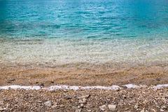 与小卵石的青绿的水海海洋背景纹理 库存照片
