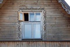与小叶子的木制框架窗口在屋顶土坎 免版税库存照片