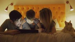 与小在家在床上和使用片剂计算机的儿子和滑稽的猫的愉快的家庭为以前打比赛 股票视频