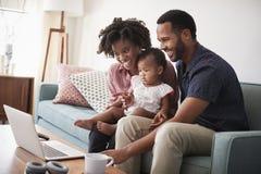 与小女儿的家庭在家坐看便携式计算机的沙发 库存照片