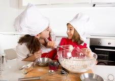 与小女儿的愉快的母亲烘烤围裙和厨师帽子的用在厨房的面粉面团 免版税库存图片