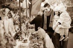 与小女孩的家庭在花卉市场上 库存图片