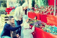 与小女孩的家庭在花卉市场上 库存照片