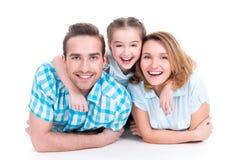 与小女孩的白种人愉快的微笑的年轻家庭 免版税库存图片