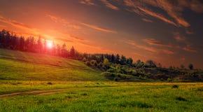 与小山的农村风景 在日落下的绿色草甸,与云彩剧烈的早晨场面的五颜六色的天空 图库摄影