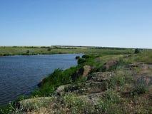 与小山的美好的绿色领域在湖附近 免版税图库摄影
