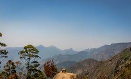 与小山范围和蓝色背景的唯一岩石 库存图片