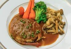 与小汤调味汁和红萝卜硬花甘蓝蘑菇边盘的小腓厉牛排牛排在葡萄酒颜色的盘 它是国际法国人c 免版税库存图片