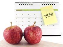 与小滴的特写镜头两苹果在木切板和饮食在被隔绝的桌面日历页计划提示消息笔记棍子 库存照片