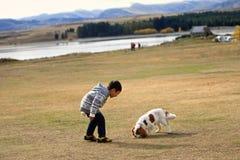 与小狗的男孩戏剧 免版税库存照片