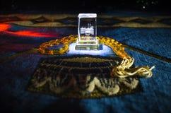 与小珠在跪垫,穆斯林Tasbih的圣洁古兰经是与一起由穆斯林传统上使用念珠的串  库存图片