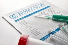 与小瓶尿容器和注射器的验血报告 免版税库存图片