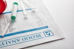 与小瓶尿容器的验血报告和注射器举起 库存图片