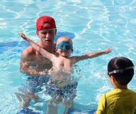 与小男孩和看守人的游泳教训 免版税库存照片