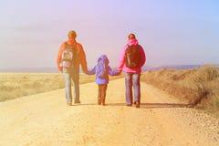 与小的儿子旅行的家庭在向山的路 免版税库存照片