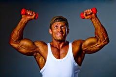 与小的哑铃的肌肉人培训 库存照片