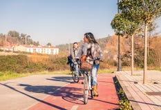 与小的女儿骑马的家庭在骑自行车 免版税库存照片
