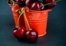 与小红色桶的成熟红色樱桃在板岩板 库存照片