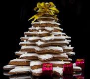 与小红色礼物的自创姜饼圣诞树在黑暗 免版税库存图片