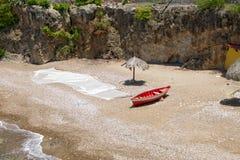 与小船、fishingnets和伞的海滩 免版税库存照片