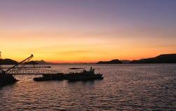 与小船和工作台的日落在前景 库存图片