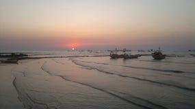 与小船的日落在与波浪的海岸 免版税图库摄影