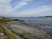 与小船的海洋岸在朱拉,苏格兰小岛  免版税库存照片