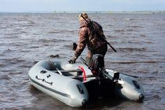 与小船的猎人在浅滩 库存图片