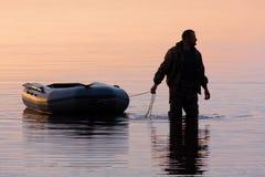 与小船的猎人 库存图片