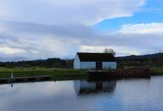 与小船的被放弃的结构在一个海湾在苏格兰高地 库存图片